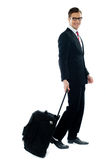 Corporate person leaving for business meeting. As he drags his luggage Stock Images