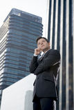 Corporate portrait attractive businessman outdoors thoughtful in business district Stock Photography