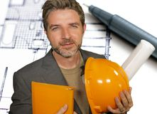 Corporate portrait of attractive efficient and confident architect man holding builder helmet and building construction blueprints stock photo