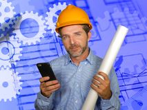 Corporate portrait of attractive efficient and confident architect man holding builder helmet and building construction blueprints royalty free stock photos
