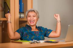 Corporate portrait of attractive and happy successful mature Asian woman working at laptop computer desk smiling confident and stock photo