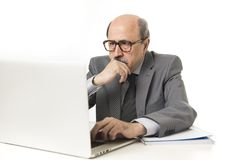 Corporate portrait bald 60s serious and bossy business man thinking and working at computer laptop office desk Royalty Free Stock Photo