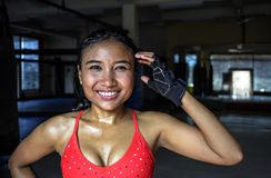 Portrait of happy beautiful and sweaty young Asian woman in sport training cloths smiling relaxed at gym. Corporate portrait of happy beautiful and sweaty young Stock Photography
