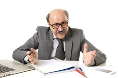 Corporate portrait of 60s bald happy business man smiling confident and satisfied sitting at computer laptop office desk working. With paperwork in job and stock photography