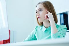 Corporate portrait of young business woman sitting at office chair working at desktop computer. stock images