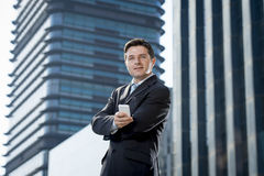 Corporate portrait of young attractive businessman with mobile phone outdoors Royalty Free Stock Images