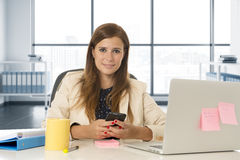 Corporate portrait young attractive businesswoman at office networking on mobile phone Royalty Free Stock Photography