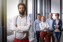 Corporate portrait of young black hipster businessman with his colleagues in background Stock Photo