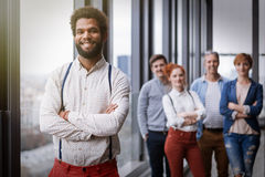 Corporate portrait of young black hipster businessman with his colleagues in background Royalty Free Stock Image