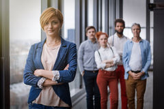 Corporate portrait of young business woman with her colleagues in background. Corporate portrait of young business women with her colleagues in background. Post Stock Photo