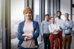 Corporate portrait of young business woman with her colleagues in background. Corporate portrait of young business women with her colleagues in background. Post Stock Images