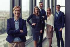Corporate portrait of young business woman with her colleagues in background. Corporate portrait of young business women with her colleagues in background. Post Royalty Free Stock Image