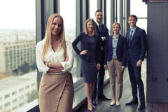 Corporate portrait of young business woman with her colleagues in background. Corporate portrait of young business women with her colleagues in background. Post Stock Photography