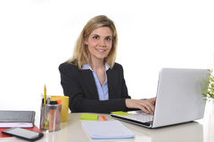 Corporate portrait young happy Caucasian blond business woman working typing on laptop computer Stock Photos