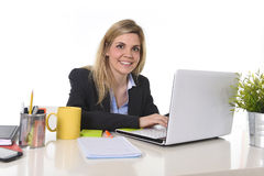 Corporate portrait young happy Caucasian blond business woman working typing on laptop computer Royalty Free Stock Photo
