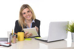 Corporate portrait young happy Caucasian blond business woman working using digital tablet pad at office Stock Photos