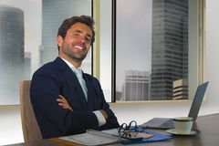 Corporate portrait of young happy handsome and attractive businessman working at computer desk in modern office at central busines stock photography