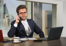 Corporate portrait of young happy handsome and attractive businessman working at computer desk in modern office at central busines royalty free stock photography