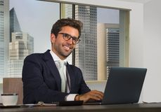Corporate portrait of young happy handsome and attractive businessman working at computer desk in modern office at central busines royalty free stock photos