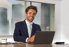 Corporate portrait of young happy handsome and attractive businessman working at computer desk in modern office at central busines royalty free stock images