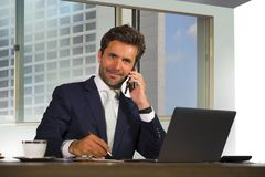 Corporate portrait of young happy handsome and attractive businessman working at computer desk in modern office at central busines stock photos