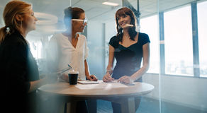 Corporate professional having an informal meeting in modern offi. Three female executives standing and discussing around a table. Corporate professional having Royalty Free Stock Images