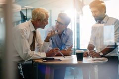 Corporate professional having a meeting in modern office. Three male executives standing and discussing around a table. Corporate professional having an informal stock photos