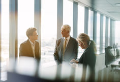 Corporate professional meeting in modern office. Three business colleagues standing behind the glass and discussing work. Corporate professional having a stock photography