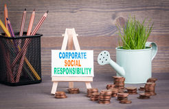 Corporate Social Responsibility Business Concept. Miniature watering pot with fresh green spring grass and small change.  Royalty Free Stock Photo