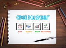 Corporate Social Responsibility. Notebooks, pen and colored pencils on a wooden table. Stock Images