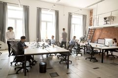 Corporate staff employees working together using computers at co. Working, busy workers group walk in motion sitting at desks in modern open space room interior stock images