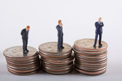 Corporate Staircase. Miniature businessmen on stacks of quarters Royalty Free Stock Photo