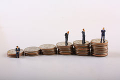 Corporate Staircase Concept. Miniature businessmen on stacks of quarters Stock Photos