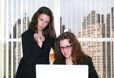 Corporate team. Two young women working together in an office enfironment Stock Photography