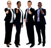 Corporate team gesturing thumbs up. Full length portrait of successful corporate team gesturing thumbs up Stock Photography
