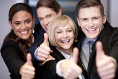 Corporate team gesturing thumbs up. Successful corporate team showing thumbs up Royalty Free Stock Photos