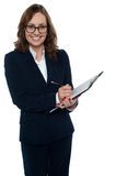 Corporate woman in eyeglasses writing on clipboard Royalty Free Stock Image