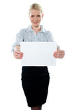 Corporate woman holding a blank billboard. Against white background Stock Photos
