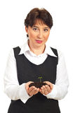 Corporate woman holding  small plant in dirt Royalty Free Stock Image