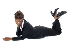 Corporate woman lying on floor, smiling Royalty Free Stock Photos