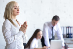 Corporate woman meditating at work Stock Photos