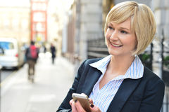Corporate woman operating her cellphone Stock Photo