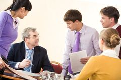 Corporate work. Image of business partners communicating at corporate meeting in office Stock Images