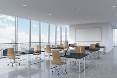 Corporate workplaces equipped by modern laptops in a modern panoramic office in New York City. Brown leather chairs and a black ta. Bles, a huge whiteboard on Royalty Free Stock Image