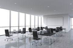 Corporate workplaces equipped by modern laptops in a modern panoramic office, white copy space in the windows. Black leather chairs and a black tables, a huge Stock Image