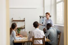 Female leader coach give presentation for diverse employees at meeting royalty free stock photo