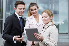 Corporation employees with tablet. Corporation employees using tablet on the street Stock Photo