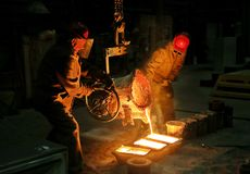 Corporation Severstal. Spilling of molten metal into molds for forgings. Workers mold metal into molds Royalty Free Stock Photography