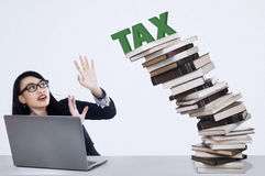 Corporation tax concept. Businesswoman and falling tax from stack of books Royalty Free Stock Photo