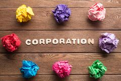 Corporation word and colorful crampled paper ball placed in circle on wooden table. Set of multiple colorful crampled paper ball placed in circle on wooden table royalty free stock photography